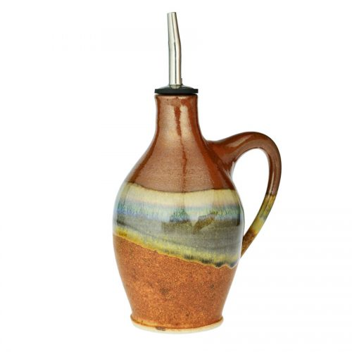 a tall, red and sandy brown oil bottle with a handle