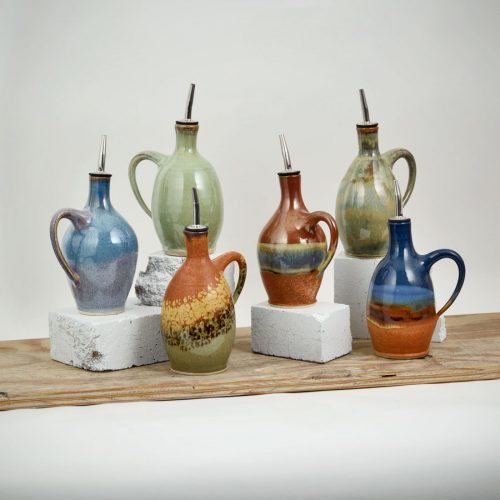 6 oil bottles with attached spouts, in assorted patterns.