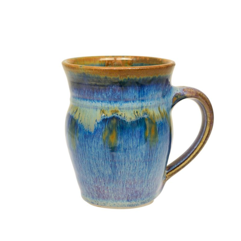 A handmade, variegated blue coffee mug with rounded sides and a bronze colored rim.