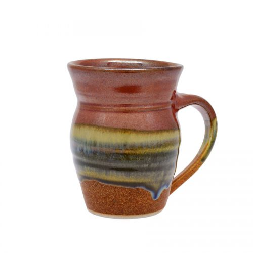 A handmade, red and sandy brown coffee mug with rounded sides and a variegated blue band across the surface.