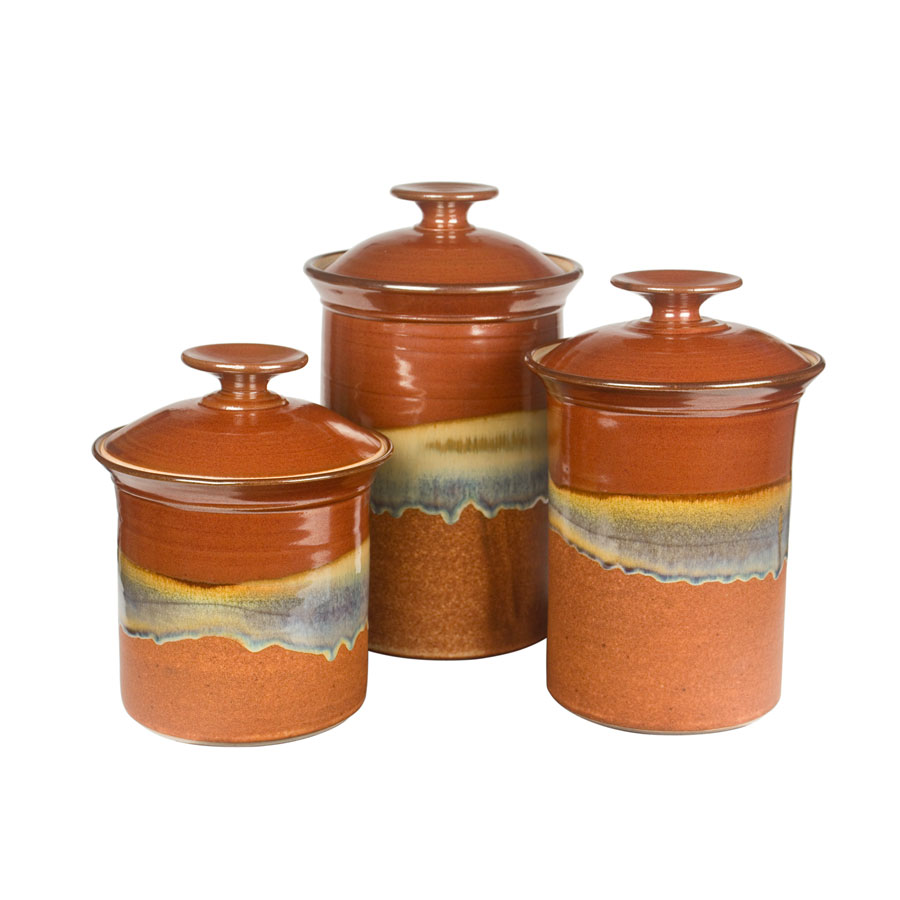 a set of red and sandy brown lidded canisters