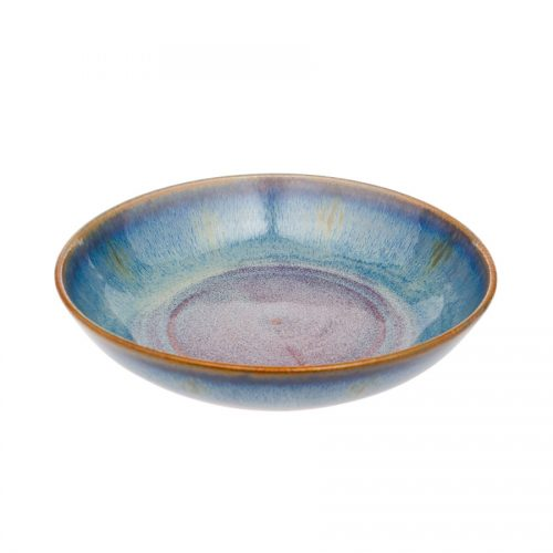 A shallow, handmade dinnerware bowl for pasta or salad. It is variegated blue with a bronze colored rim.