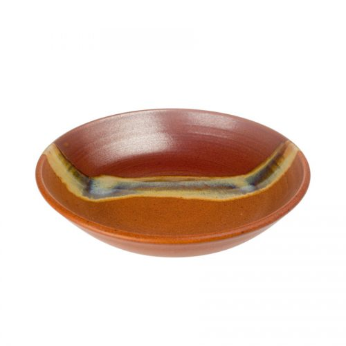 A shallow, handmade dinnerware bowl for pasta or salad. It is red and orange with a pale blue band across a third of the pottery.