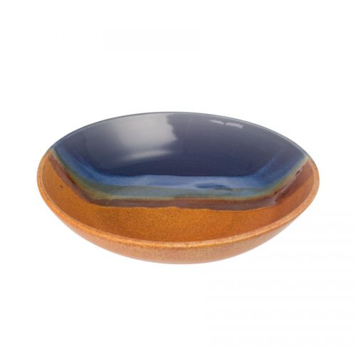 A shallow, handmade dinnerware bowl for pasta or salad. It is blue and orange with a pale blue band across a third of the pottery.