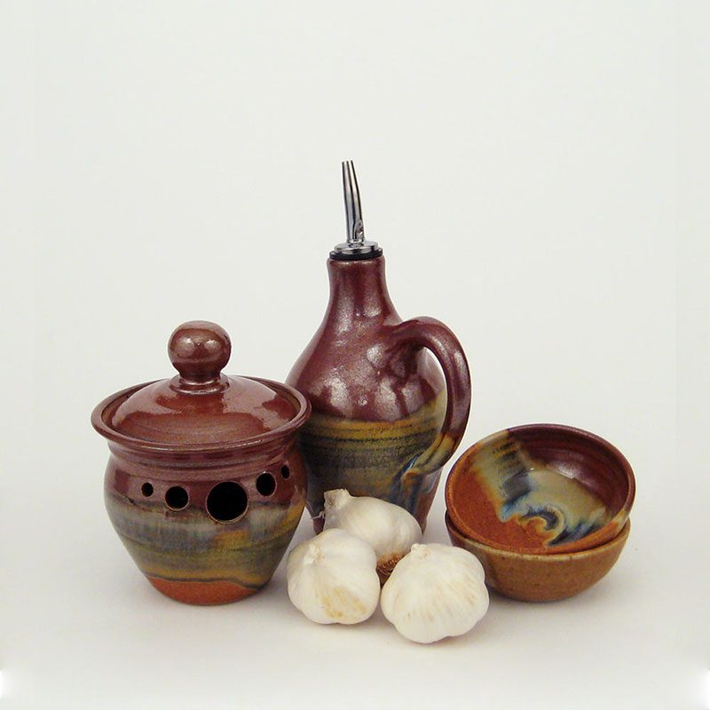 Garlic Jar, Oil Bottle, and Spice Dishes that are a glossy red on top, sandy orange on bottom, with a drippy blue horizontal band dividing the two halves of each piece.