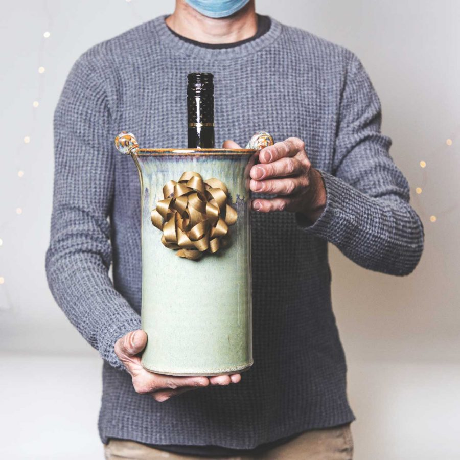 A person holding out a handmade green wine caddy with a gold bow.