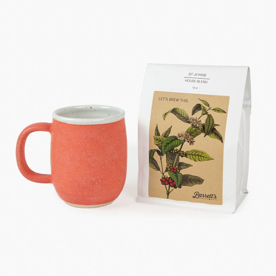 A coral colored mug with a 12 oz. bag of coffee