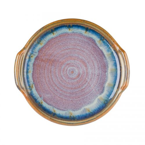 A handmade, round, variegated blue serving tray with handles and a bronze colored rim.