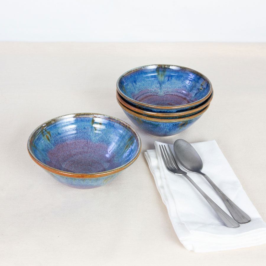 a set of small blue ceramic dinnerware bowls on a tablecloth.
