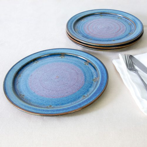 a set of 4 blue handmade dinnerware plates on a tablecloth.