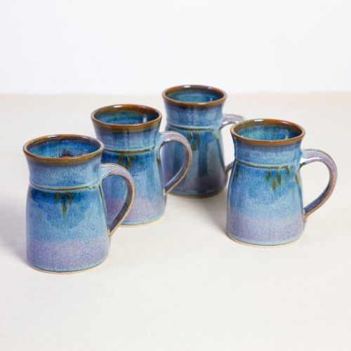 A set of 4 handmade blue flare sided mugs on a tablecloth.