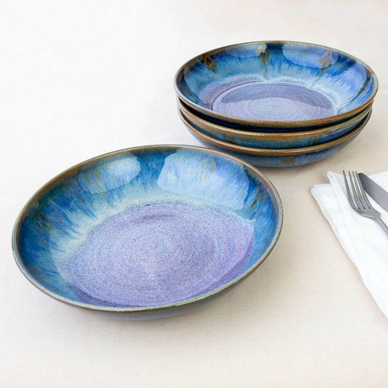 a set of 4 blue shallow dinnerware bowls on a tablecloth.