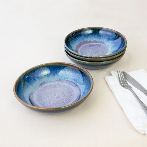 a set of 4 small blue shallow handmade bowls on a tablecloth.