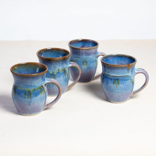 A set of 4 handmade blue round sided mugs on a tablecloth.