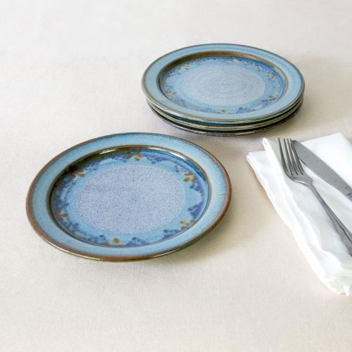 a set of 4 small blue ceramic dinnerware plates on a tablecloth.