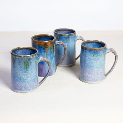 A set of 4 handmade blue straight sided mugs on a tablecloth.