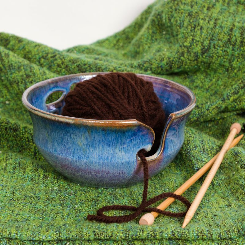 A blue handmade yarn bowl on a green knitted blanket.