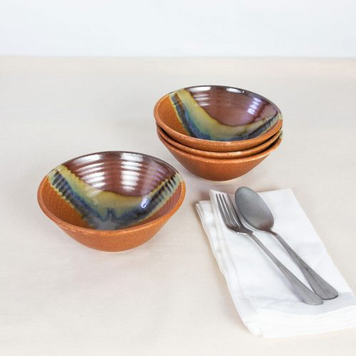 a set of 4 small red and orange ceramic dinnerware bowls on a tablecloth.