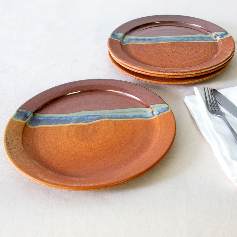 a set of 4 red and orange handmade dinnerware plates on a tablecloth.