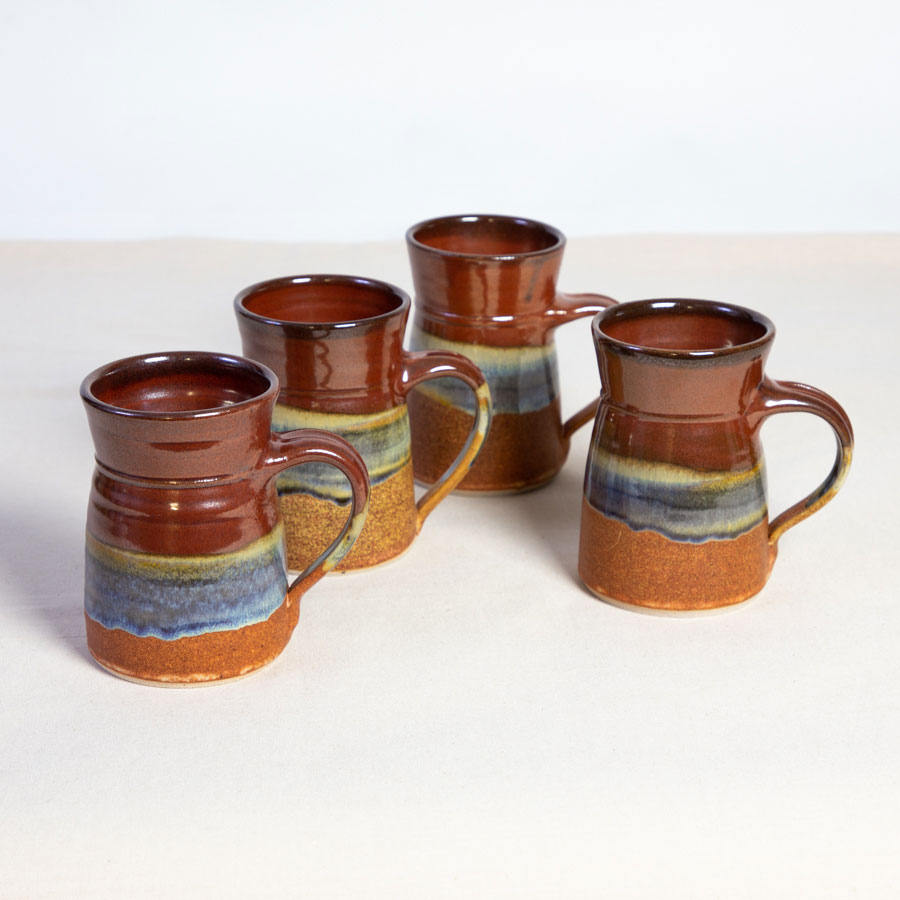 A set of 4 handmade red and orange flare sided mugs on a tablecloth.