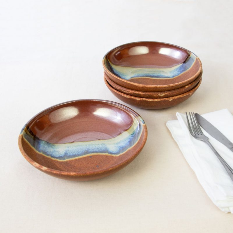 a set of 4 small red and orange shallow handmade bowls on a tablecloth.