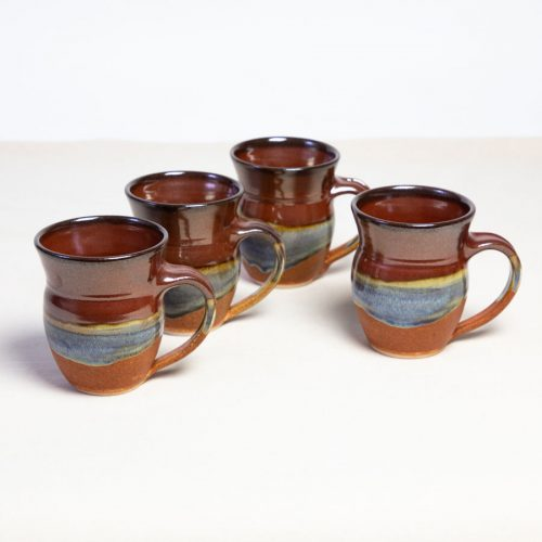 A set of 4 handmade red and orange round sided mugs on a tablecloth.