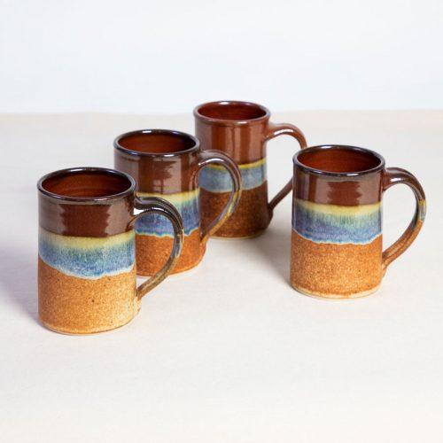 A set of 4 handmade red and orange straight sided mugs on a tablecloth.
