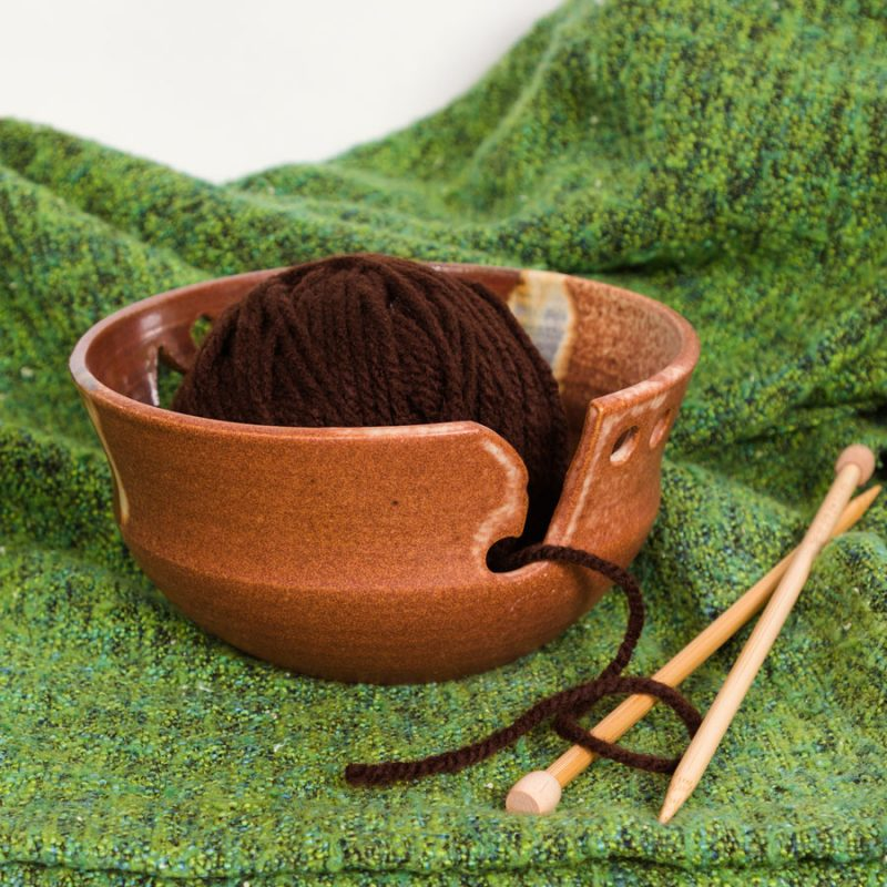 An orange and red handmade yarn bowl on a green knitted blanket.