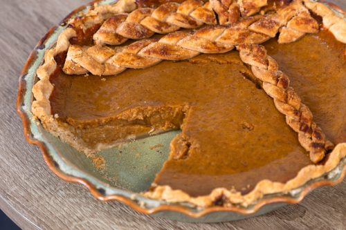 a closeup of a handmade pale green pie plate with a homemade pumpkin pie that has a slice cut out of it.