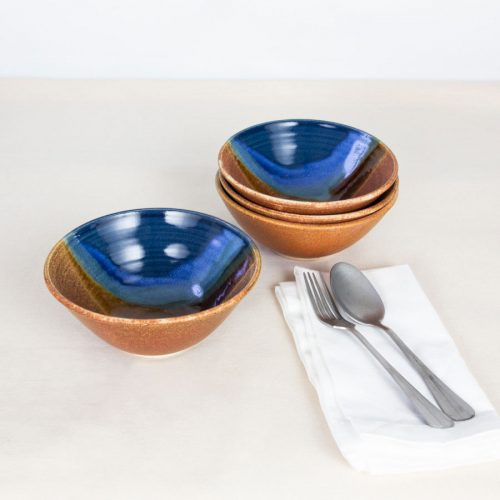 a set of 4 small blue and orange ceramic dinnerware bowls on a tablecloth.