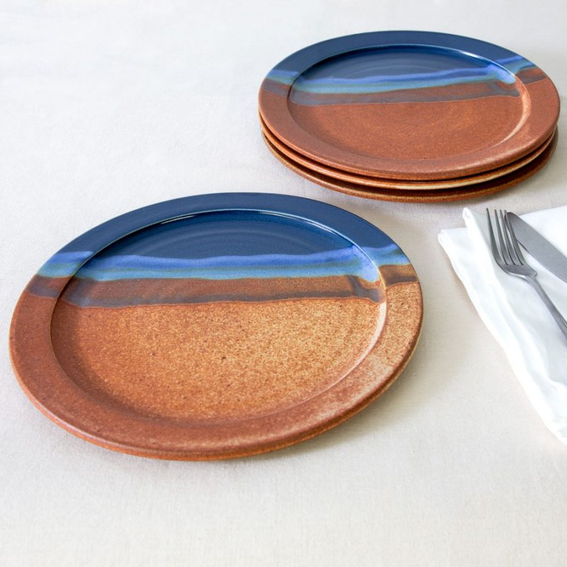 a set of 4 blue and orange handmade dinnerware plates on a tablecloth.