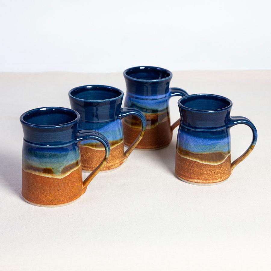 A set of 4 handmade blue and orange flare sided mugs on a tablecloth.