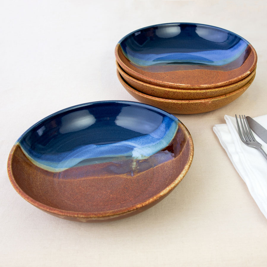 a set of 4 blue and orange shallow dinnerware bowls on a tablecloth.