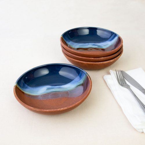 a set of 4 small blue and orange shallow handmade bowls on a tablecloth.