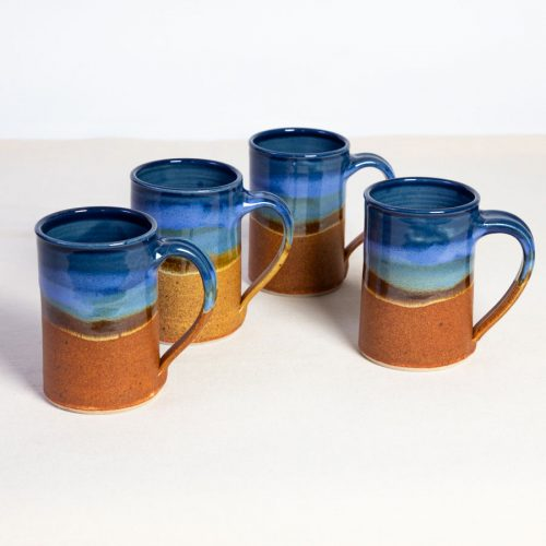 A set of 4 handmade blue and orange straight sided mugs on a tablecloth.