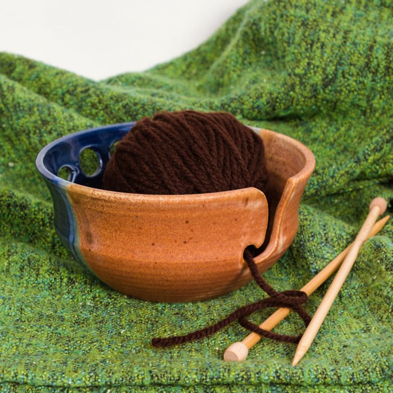 An orange and blue handmade yarn bowl on a green knitted blanket.