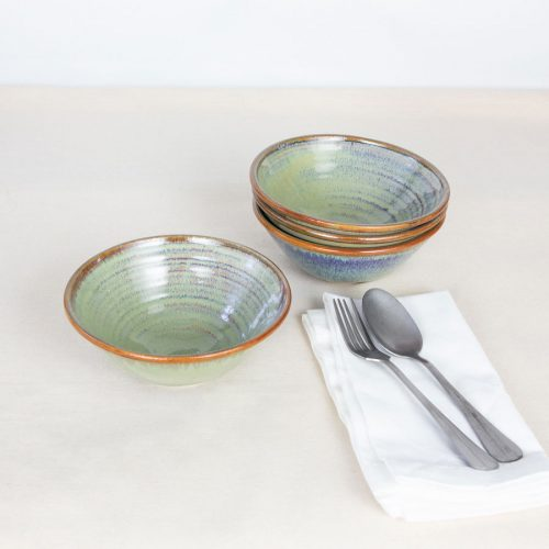 a set of 4 small pale green ceramic dinnerware bowls on a tablecloth.