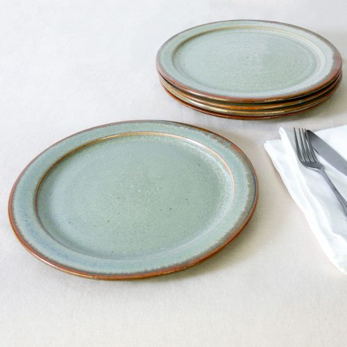 a set of 4 pale green handmade dinnerware plates on a tablecloth.