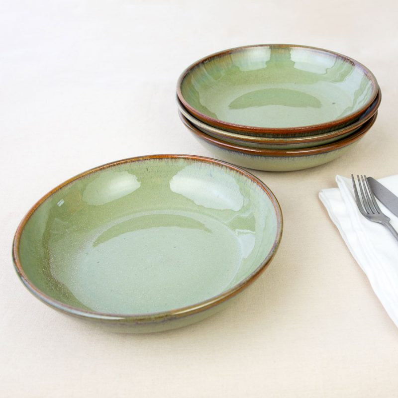 a set of 4 pale green shallow dinnerware bowls on a tablecloth.