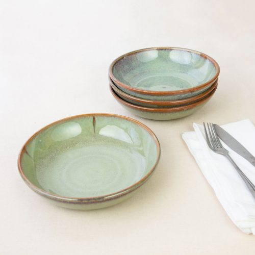 a set of 4 small pale green shallow handmade bowls on a tablecloth.