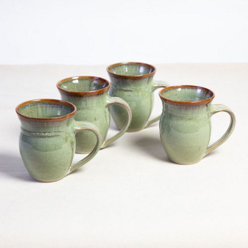 A set of 4 handmade pale green round sided mugs on a tablecloth.