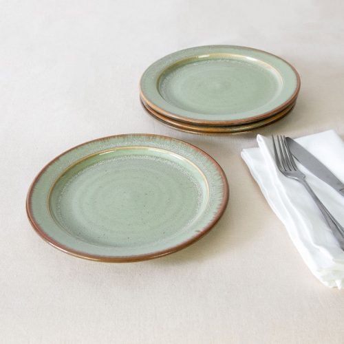 a set of 4 small pale green handmade dinnerware plates on a tablecloth.