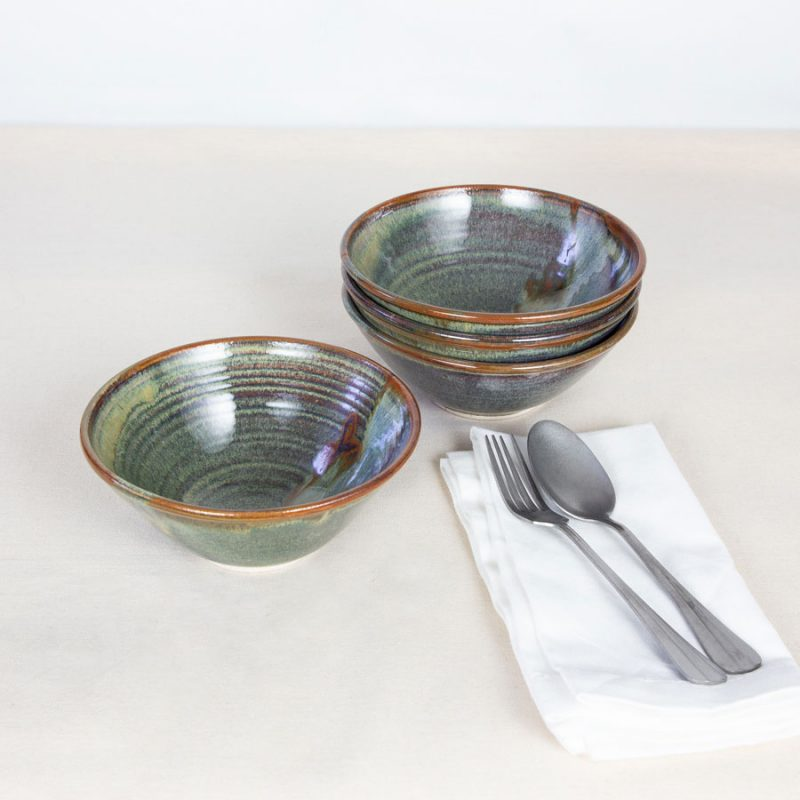A set of small green ceramic dinnerware bowls on a tablecloth.