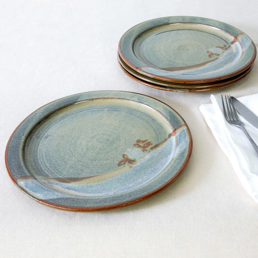 a set of 4 green handmade dinnerware plates on a tablecloth.