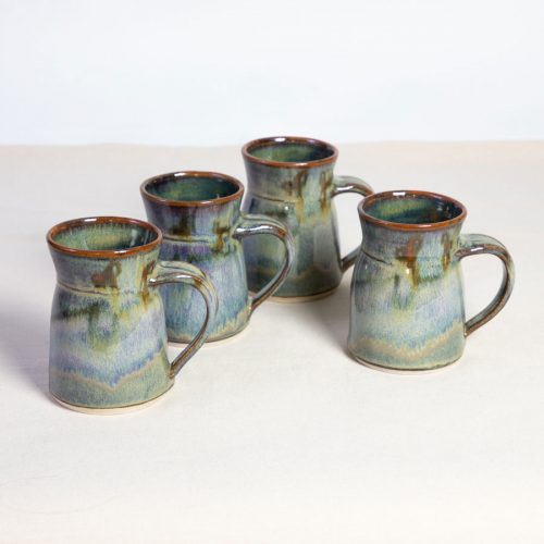 a set of 4 handmade green flare sided mugs on a tablecloth.