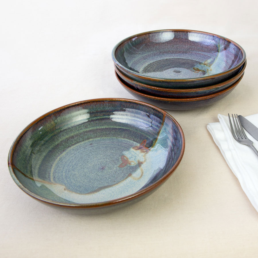 a set of 4 green shallow dinnerware bowls on a tablecloth.