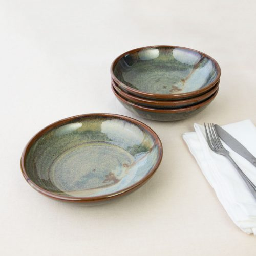 a set of 4 small green shallow handmade bowls on a tablecloth.