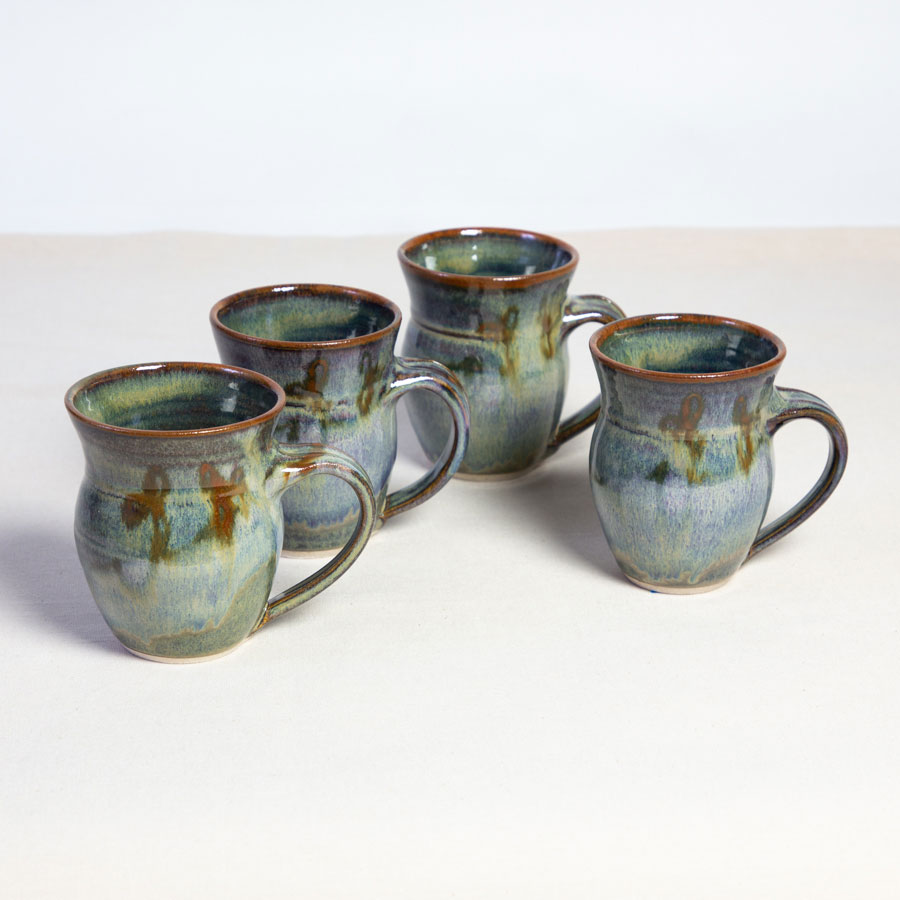 A set of 4 handmade green round sided mugs on a tablecloth.