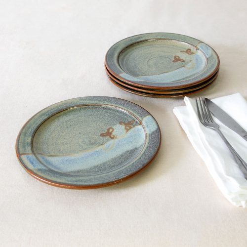 a set of 4 small green handmade dinnerware plates on a tablecloth.