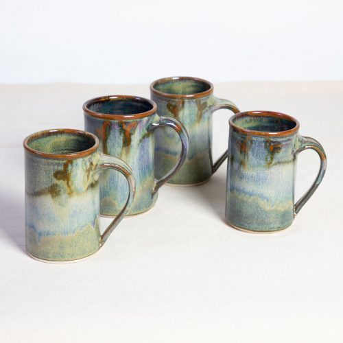 A set of 4 handmade green straight sided mugs on a tablecloth.